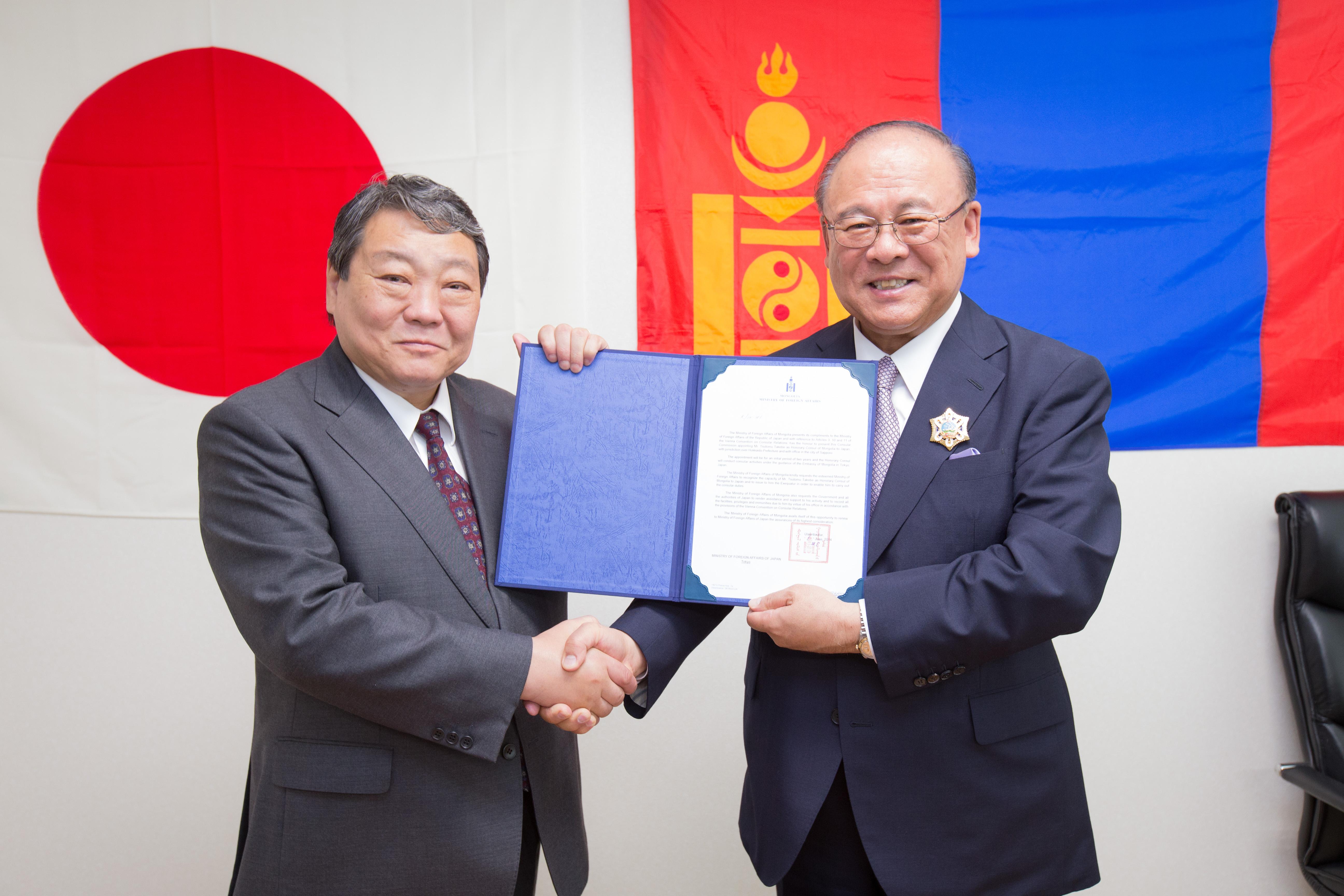 ソドムジャブツ・フレバータル  モンゴル大使(左)から辞令を与る